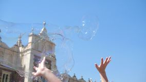 Cheery soap bubbles are caught by laughing children in Krakow square in summer