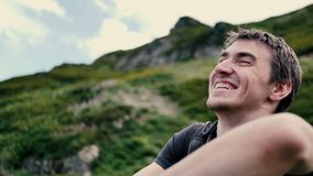 Happy man turning aside and smiling in the Georgian Mountains in summer in slo-mo. Cheery view of a young fair-haired Caucasian man with a short haircut in a T stock video