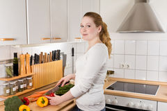 Cheery woman kitchen cutting vegetables Stock Photography