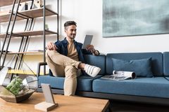 Cheery youthful guy relaxing at his aprtment Stock Image