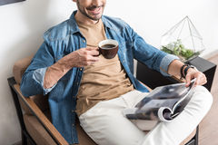 Cheery youthful guy resting with mug of hot beverage indoor Royalty Free Stock Image