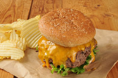 Cheesburger. A cheeseburger and potato chips on butcher paper Stock Photos
