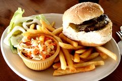 Cheesburger and french fries. Cheeseburger with onions and french fries on the table Stock Photo