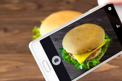 Cheesburger on the screen of smartphone Stock Photography