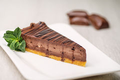 Cheescake del chocolate o del café con la hoja de la menta en la placa blanca, torta libre del gluten, fotografía del producto pa fotografía de archivo libre de regalías