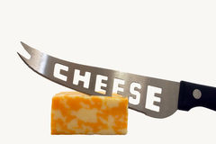 Cheese. A chunk of colby jack cheese with a cheese knife stuck in it against a white background Royalty Free Stock Photos