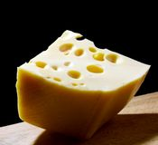 Cheese. Piece of cheese in light over black background Stock Photos