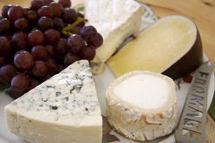 Cheese. Four different cheeses with grapes on platter Stock Photo