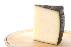 Cheese. Portion of a typical Spanish cheese with black rind. On a wooden plate stock photography