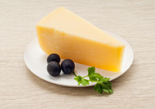 Cheese. Firm cheese on a white round plate with parsley and olives on a cloth Stock Images