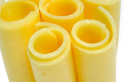 Cheese. Some rolled cheese slices on a white background Royalty Free Stock Images