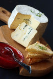 Cheese. Delicious cheese, cranberry jam and toasts on a wooden board Royalty Free Stock Photos