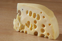 Cheese. Piece of cheese close-up on beige wood surface Royalty Free Stock Photography