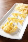 Cheese. Of different shapes on the dish. Focus on the first one Stock Image