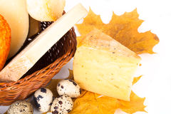 Cheese allsorts in a wicker basket on yellow autumn leaves on a Stock Photos