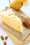 Cheese with almonds and pear on a cutting board Stock Photo