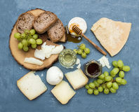 Cheese appetizer selection or wine snack set. Variety of italian cheese, green grapes, bread slices and honey on round Stock Photography