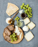 Cheese appetizer selection or wine snack set. Variety of italian cheese, green grapes, bread slices and honey on round Stock Image