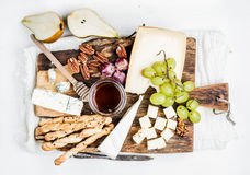 Cheese appetizer set. Various types of cheese, honey, grapes, pear, nuts and bread grissini sticks on rustic wooden royalty free stock images
