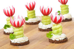 Cheese appetizers. Decorated cheese appetizers: Spiced cream cheese with spiral cucumber and radishes blossoms on pumpernickel Stock Image