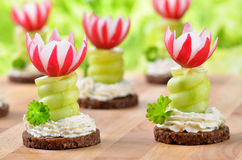 Cheese appetizers. Decorated cheese appetizers: Spiced cream cheese with spiral cucumber and radishes blossoms on dark wholegrain bread, wooden cutting board Stock Photo