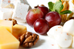 Cheese in the assortment of grapes and walnuts Royalty Free Stock Image