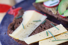 Cheese, avocado and radish sandwich on black bread Royalty Free Stock ...
