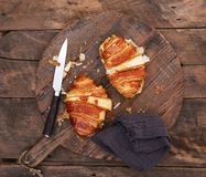 Cheese and bacon croissant on a wooden cutting board with knife stock photos