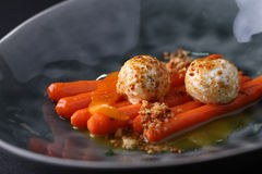 Cheese balls served on carrot with sauce in dark deep plate. Closeup Royalty Free Stock Photo