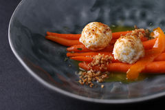 Cheese balls served on carrot with sauce in dark deep plate. Closeup Stock Photo