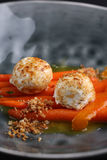 Cheese balls served on carrot with sauce in dark deep plate. Closeup Royalty Free Stock Photography
