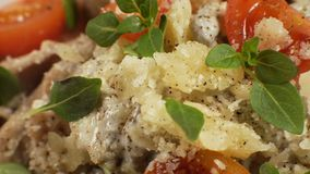 Cheese, basil leaves and cherry on pasta. Video. Horizontal stock footage