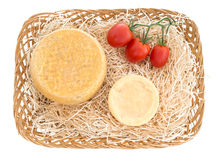 Cheese basket with red tomatoes over white background. Stock Image