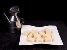 Cheese and Beaker. A beaker and pieces of Parmesan cheese in a white dish, on a black background Royalty Free Stock Photo