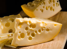 Cheese with big holes on wooden board Stock Images