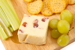 Cheese and Biscuits. Wenslydale cheese with cranberries on a wooden board with crackers and garnish Stock Photo