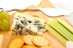 Cheese and Biscuits. Close up of a piece of Roquefort blue cheese on a wooden cheeseboard Royalty Free Stock Photo