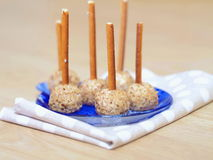 Cheese bites. Cheesy appetizer decorated with ground nut and pretzel sticks. Party food. Selective focus on the front Stock Image