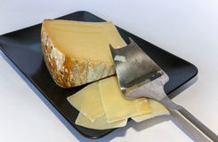 Cheese on a black plate sliced Stock Photo