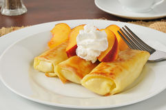 Cheese blintzes with peaches and cream Royalty Free Stock Photos