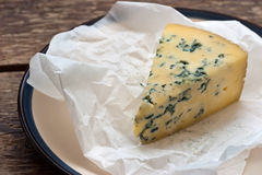 Cheese with a blue mold on the paper Stock Image