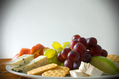 Cheese board. An assortment of cheese served with fresh fruit Stock Image