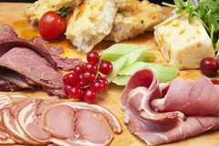 Cheese Board. Cuts of fine cured meats on a cheese board. Lamb, Ham and Pastrami Royalty Free Stock Photo