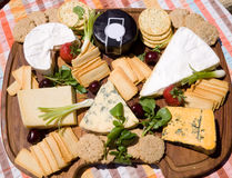 Cheese board. With crackers fuit and salad in the summer sunshine Stock Photo