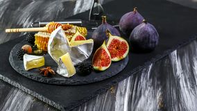 Cheese Board, Camembert with figs and honey. Cheese Board,Camembert with figs and honey and white wine.selective focus royalty free stock photos