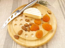 Cheese board. Cheeseboard. Camembert, dried apricots and almonds Royalty Free Stock Images