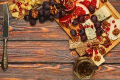 Cheese board concept. Cheese board with different varieties of ripe cheese served with grapes, grapefruit and garnet, walnuts and crackers on wooden table in Stock Image