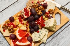 Cheese board with fruits. Refined cheese board - roquefort, camembert, parmesan and cheddar with grapes, grapefruit, walnuts, garnet and rye crackers. Excellent Royalty Free Stock Photos