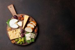 Cheese board. With grapes and nuts. Wine snaks. Top view with space for your text royalty free stock images