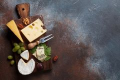 Cheese board. With grapes and nuts. Wine snaks. Top view with space for your text royalty free stock photo
